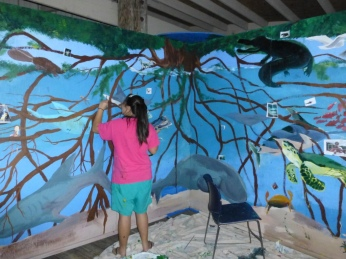 Volunteers painting a mural
